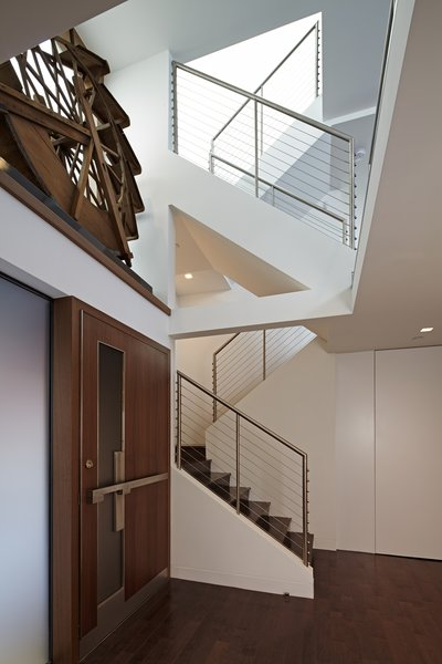 Inside, a ledge above the door holds an antique water wheel, a notable piece belonging to the Client.  This wheel is backlit with a large window adjacent to it.  Top floor skylights add dramatic light which filters down a multi-tiered staircase.     Photo 3 of Perrin Residence modern home