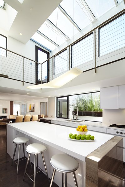 The central two-story kitchen is washed with light from multiple skylights, which also filter into the adjoining living and dining rooms. Photo 5 of Perrin Residence modern home