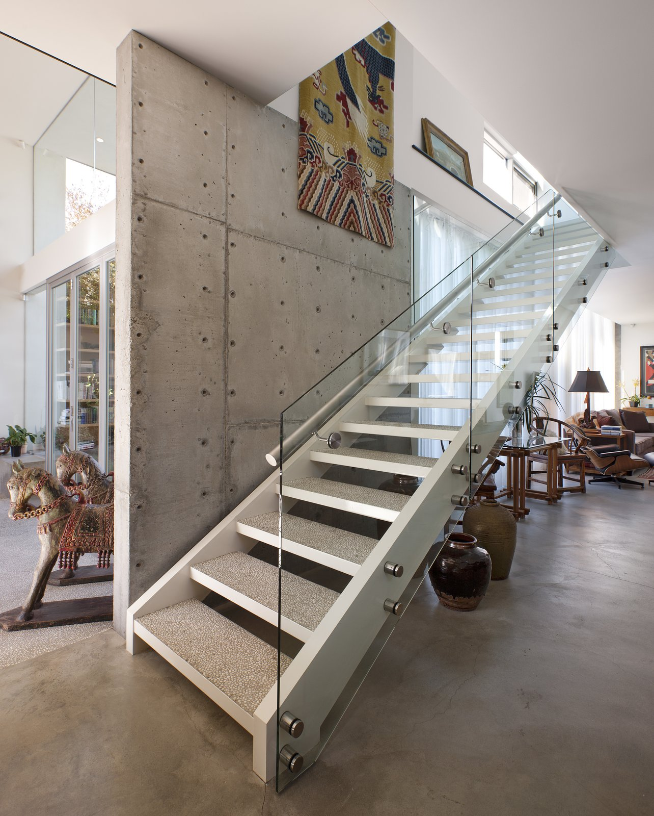 The staircase also serves as a divider between the glass half of the home, on the left, and the more solid counterpart, on the right.