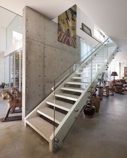 The staircase also serves as a divider between the glass half of the home, on the left, and the more solid counterpart, on the right.  Photo 5 of Goodman Residence modern home