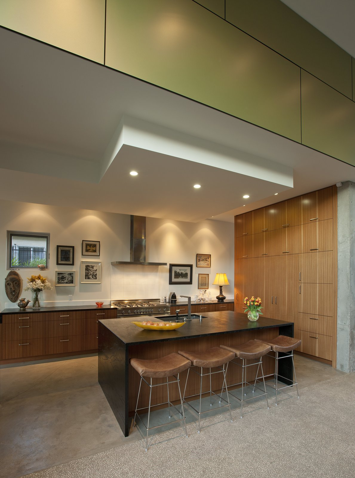 The Mid-Century style kitchen is recessed, framed in the same green Trespa panels on the exterior of the home, further incorporating an indoor-outdoor setup that is popular in Venice Beach.