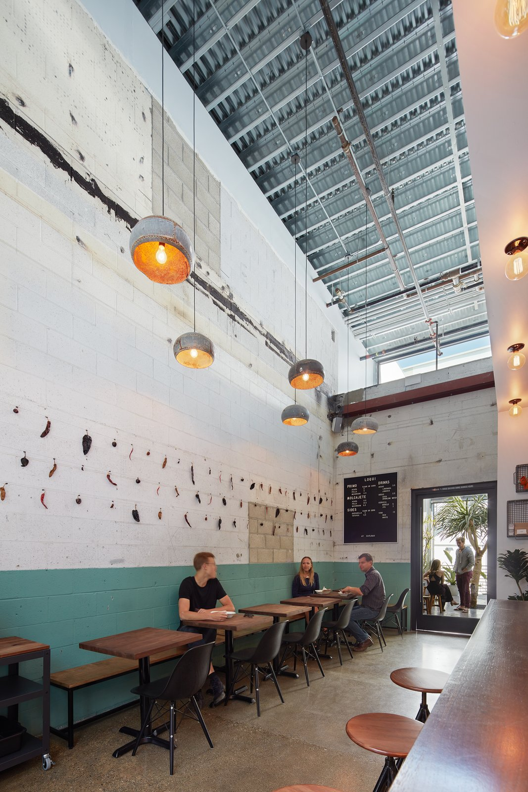 The interiors of the repurposed car bays show their industrial background.  This taco bar, also designed by Abramson Teiger Architects, has raw cinder block on the walls leftover from its car repair roots.   PLATFORM by Abramson Teiger Architects