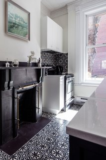 "Historic Montreal House Meets DIY IKEA - Photo 4 of 5 - ""We tried to keep the integrity of the [original] interior,"" Havart says. ""We placed some cabinets around the beautiful but nonfunctional chimney."" The oven is by Frigidaire."