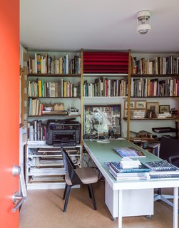 The space holds a library of books and a work table for two.