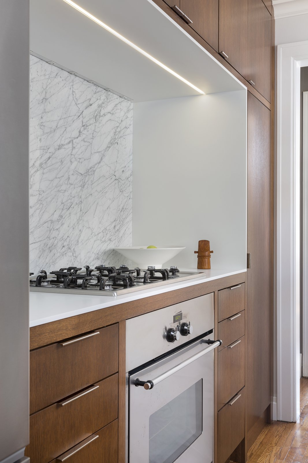 Another custom oak unit houses the oven, range, refrigerator, and pantry. Tagged: Kitchen, Wood Cabinet, Medium Hardwood Floor, Marble Backsplashe, Range, and Accent Lighting.  Photo 4 of 10 in How to Make Your Tiny Kitchen Feel Huge in 6 Easy Steps from Rebooting One Kansas House at a Time
