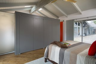 Rebooting One Kansas House at a Time - Photo 7 of 10 - Fein was tasked with reimagining a master suite in a ranch house in Mission Hills, Kansas. A wall of handleless cabinets serves as the closet, subtly dividing the space from the bath area.