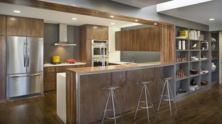 Rebooting One Kansas House at a Time - Photo 9 of 10 - In a 1960s house in Overland Park, Kansas, Forward Design | Architecture remodeled a kitchen, family room, and mudroom. Walnut cabinets integrate the appliances to create a seamless look.