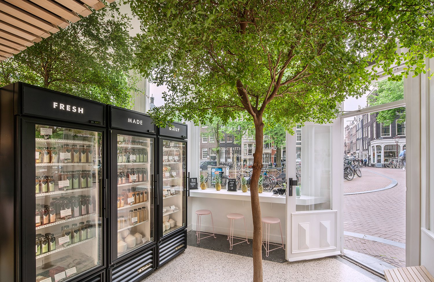In Amsterdam's Nine Streets neighborhood, the roughly 250-square-foot shop of Cold Pressed Juicery showcases a vibrant tree in the middle of the space. Photo by Wouter van der Sar. A Tree Grows in Amsterdam - Photo 6 of 7