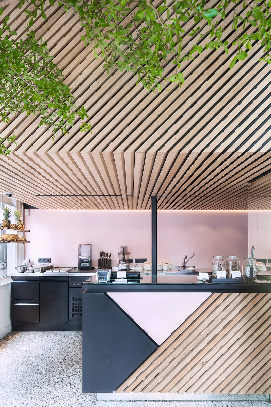 Designed by Standard Studio, the graphic store uses a palette of black and pink powder-coated metal and diagonally aligned wood slats. Photo by Wouter van der Sar.  Interiors by Chase Daniel from A Tree Grows in Amsterdam