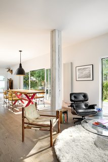 A playful approach to furnishings defines the interior. A mix of traditional items and modern pieces, among them an Eames chair and Warren Platner coffee table in the living area, fills the home. What looks like an exposed wood beam column in the open-plan living and dining space is in fact a pillar covered in wallpaper.