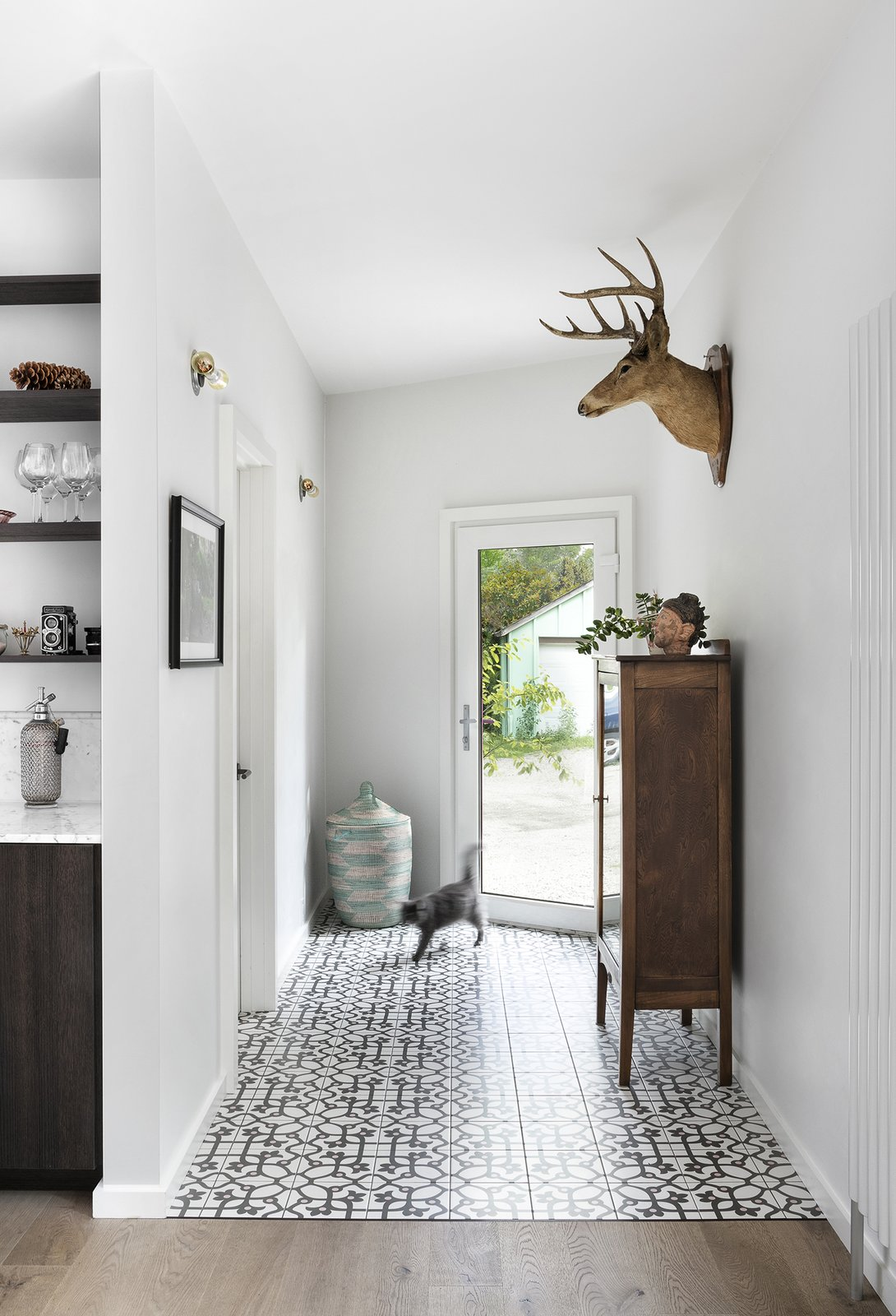Jujol Basalto porcelain tiles, sourced from Mettro Source, line the floor just inside the front entry.