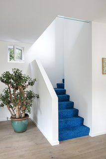 Cobalt blue carpet by Object Carpet leads to the second floor.