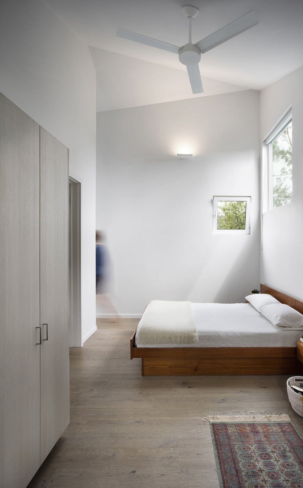 Highlighting the home's asymmetrical geometry, the design team decided to use a range of window sizes throughout. Tagged: Bedroom, Bed, and Medium Hardwood Floor.  Photo 7 of 8 in Quirky Toronto House Is Far From Color Shy