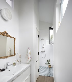 Quirky Toronto House Is Far From Color Shy - Photo 7 of 7 - The en-suite master bathroom features an IKEA vanity and a curbless shower clad in Palau Celeste tile.