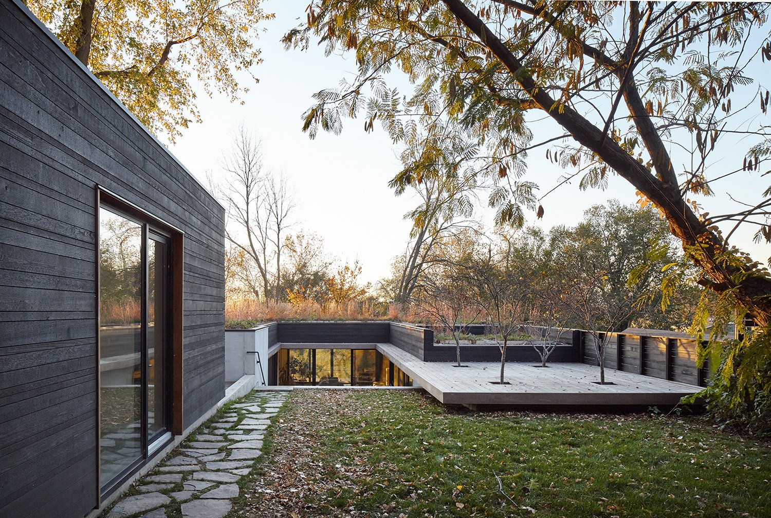 The roof, which extends into a deck, appears to float above the ground. A detached studio building is located on the site's upper level. Tagged: Exterior, House, and Wood Siding Material.  Photo 2 of 9 in Nature Reigns Supreme at a Verdant Kansas City Home