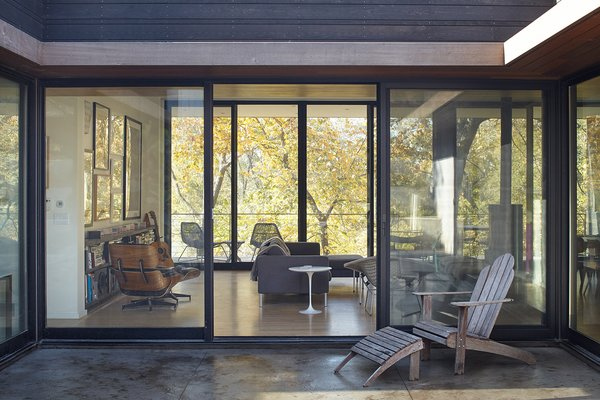 Large sliding doors connect the living room to both the courtyard and a covered porch on the western side of the house.