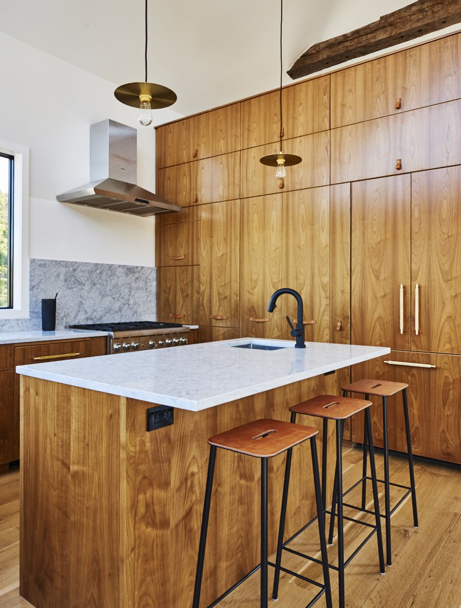 European walnut lines the custom kitchen, which is outfitted with Blum and Hafele hardware, a Brizo faucet, and pendants by Danish studio Frama. The range is Thermador. Tagged: Kitchen, Wood Cabinet, Marble Counter, Pendant Lighting, and Marble Backsplashe.  Photo 5 of 7 in You Won't Lose Your Wi-Fi Connection at This Hamptons Retreat