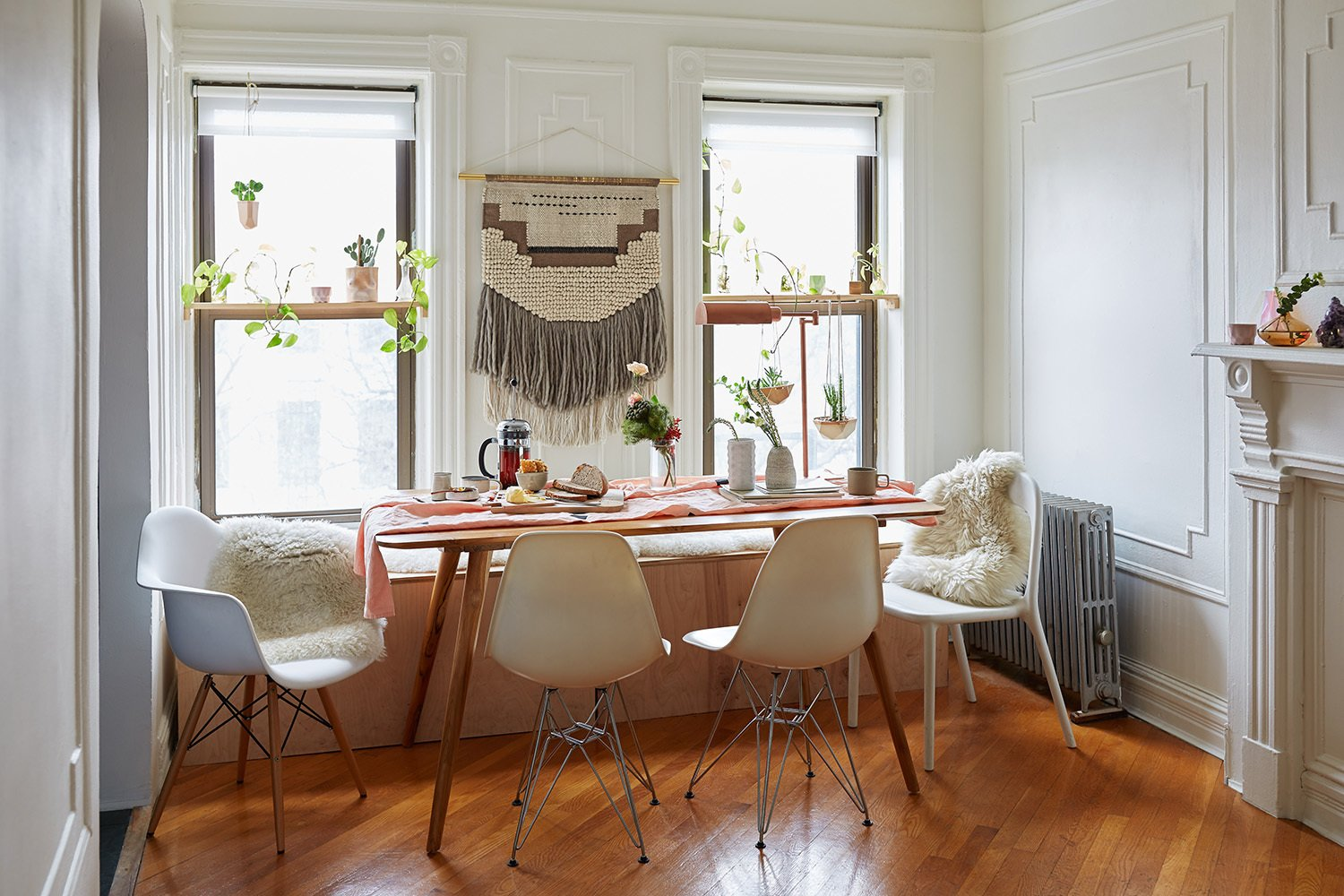 The couple's changes to the space were mostly decorative. They built the custom bench in the dining area, which holds a litter box for their cat on one end and storage space on the other. The table was purchased at The Source in Brooklyn and the wall hanging is from CB2.
