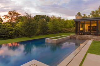 Forging a Connection to the Texas Skies One Window at a Time - Photo 2 of 3 - To enhance the home's floating effect, the rear yard features a pool that conceptually emerges from additional small pools of water that extend from under the house. Once the water reaches the backyard, it then flows over the infinity edge and back onto the landscape. Courtesy of Marvin Windows and Doors.