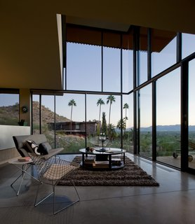 Taking it to the Desert With Dwell Home Tours - Photo 2 of 12 - With floors made of cork and concrete, the house is surrounded by substantial panels of translucent glass. The double-height living room acts as a collective open space that looks out to the dramatic views of the desert.
