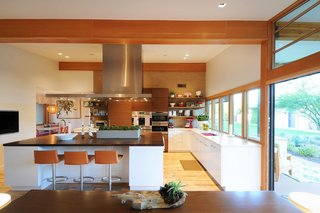 Taking it to the Desert With Dwell Home Tours - Photo 11 of 12 - Throughout the house, Woolsey opened up confined rooms to create spacious areas where the family can live and play together. One example is shown here, where she expanded the kitchen by connecting it to a banquet breakfast area.