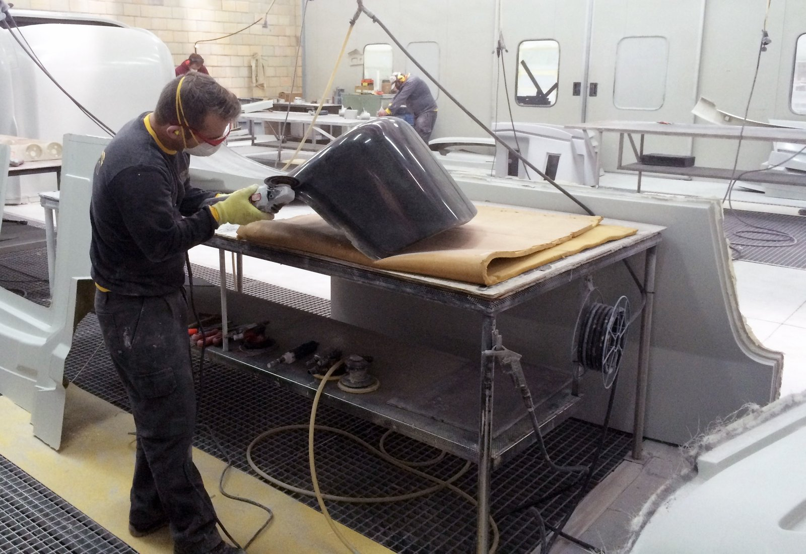 The pieces are designed in Italy and manufactured in Portugal, where De La Espada's workshop is known for their high-quality woodworking skills. Shown here is a craftsman at work, carefully sanding the fiberglass shells that are fabricated through multiple steps—from forming a mold to the final piecing together.  Photo 7 of 8 in Bringing Back a Forgotten Material