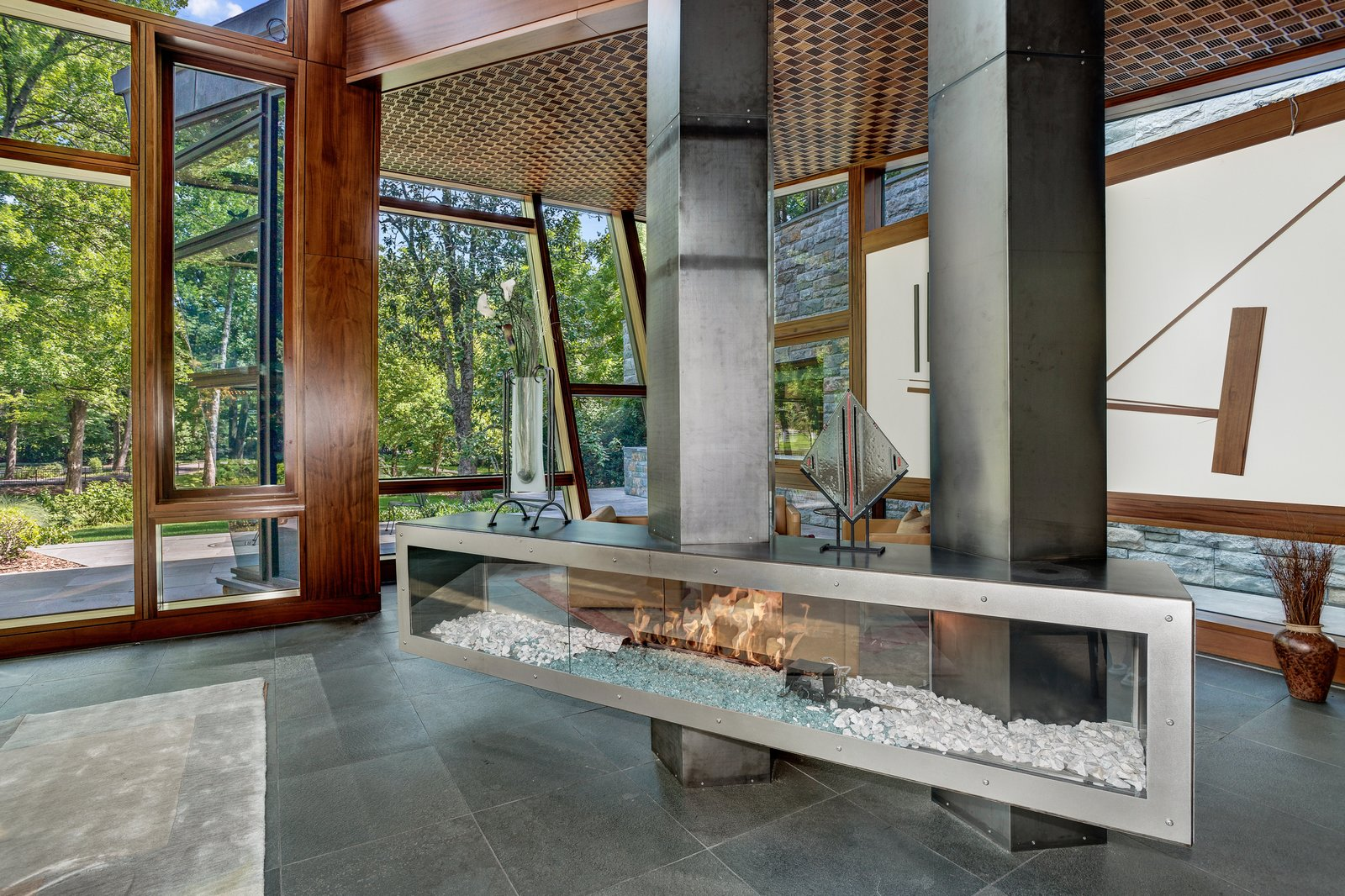 Designed by architect David Jameson in the heart of Bethesda, Maryland, this sculptural residence is filled with bespoke elements that are made up of wood, metal, stone, and glass. The centralized fireplace divides the open living space into two separate seating areas, without closing them off from one another.  97+ Modern Fireplace Ideas by Dwell from Proof That a Modern Fireplace Can Be the Defining Factor of a Space