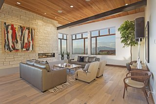 This modern mountain escape is outfitted with cutting-edge technology and sits seamlessly within the landscape of Woodland Hills, Utah. Its immense vistas are accentuated by a sleek fireplace that's surrounded by a more organic placement of stone.