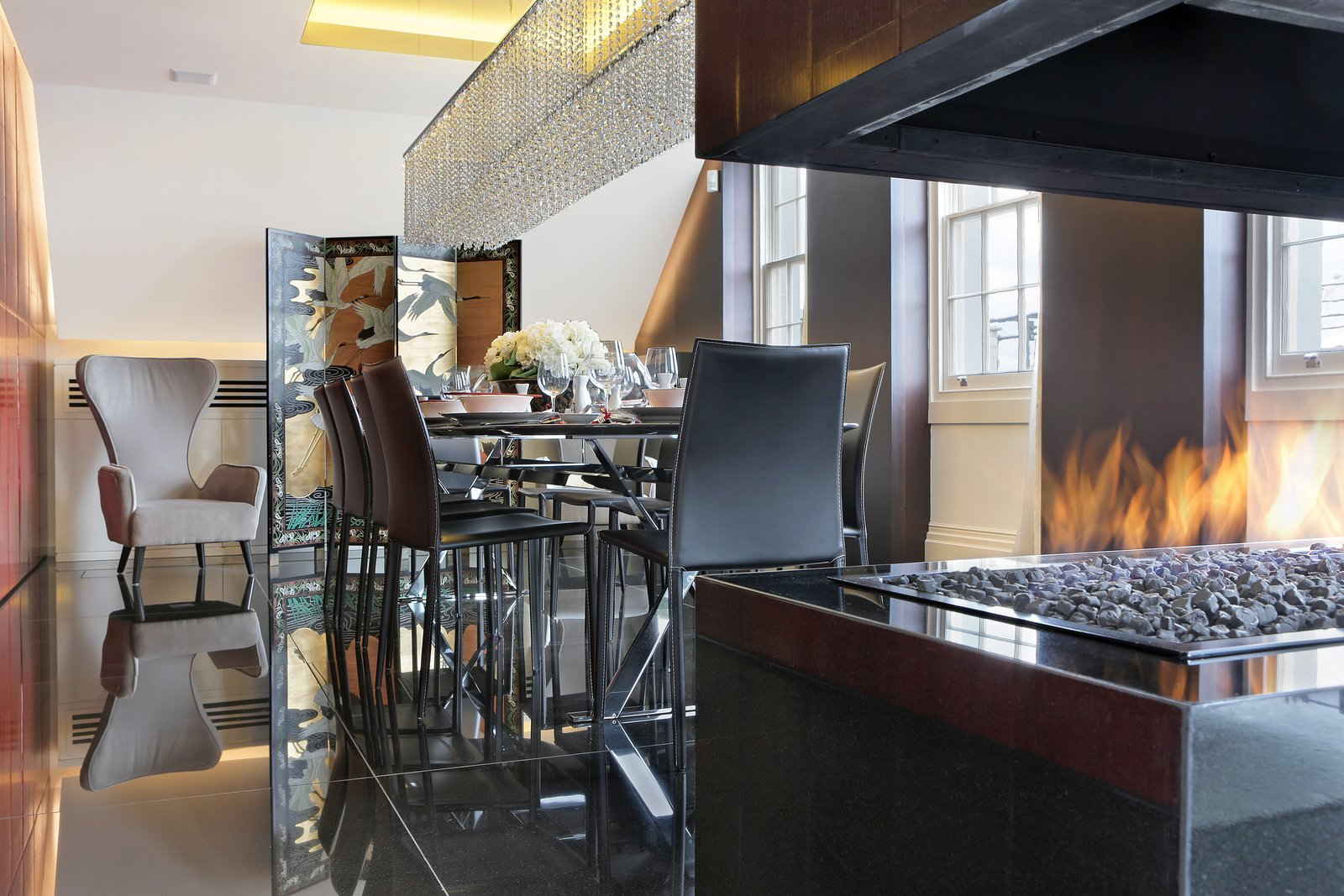 Overlooking London's St. James's Park, the penthouse of the Carlton House Terrace features 24-hour security and a private entrance with a concierge desk. Elevator access leads you to this renovated residence where the open stacked fireplace takes command of the dining room.  97+ Modern Fireplace Ideas by Dwell from Proof That a Modern Fireplace Can Be the Defining Factor of a Space