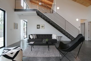 A Passion for Design Guides the Creation of a Nordic-Inspired Home - Photo 2 of 9 - The living space sits underneath metal stairs that lead up to the mezzanine. Loewinger worked with a local metalworker to create the staircase. She purchased the furnishings from both HD Buttercup and CB2.