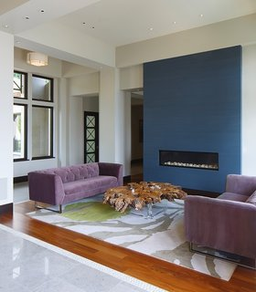This House Takes on Gusty Winds and an Earthquake Fault - Photo 4 of 9 - A closer look at the living space near the entrance reveals a modern fireplace that's built into a blue accent wall.