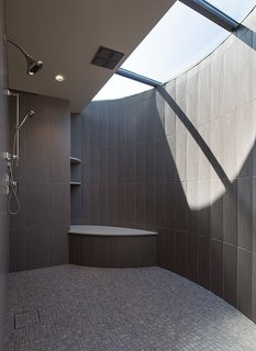 This House Takes on Gusty Winds and an Earthquake Fault - Photo 7 of 9 - For the master bathroom, he worked with a fabricator to design a custom crescent-shaped skylight that lets light stream into the shower.