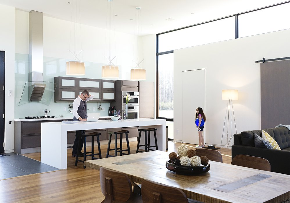 """Goldstein and his youngest daughter Sari are shown here in the open kitchen that flows into the great room, which has become the main space where the family spends time together. In the video below, Goldstein starts out by explaining how integrated smart home technology """"allows you to have an intuitive relationship with the architecture."""" He knew SAGE's wireless interface could help get the job done."""