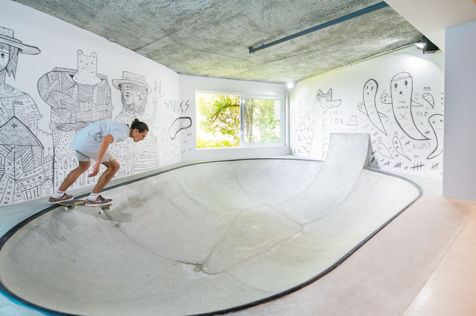 A fully functional concrete skate bowl plays a quintessential role in the layout and movement of the space. With walls lined with custom art by South African street artist Jack Fox, the playful quality of the space is achieved.  Photo 2 of 6 in A Skateboarding Devotee Gets the Lounge of His Dreams