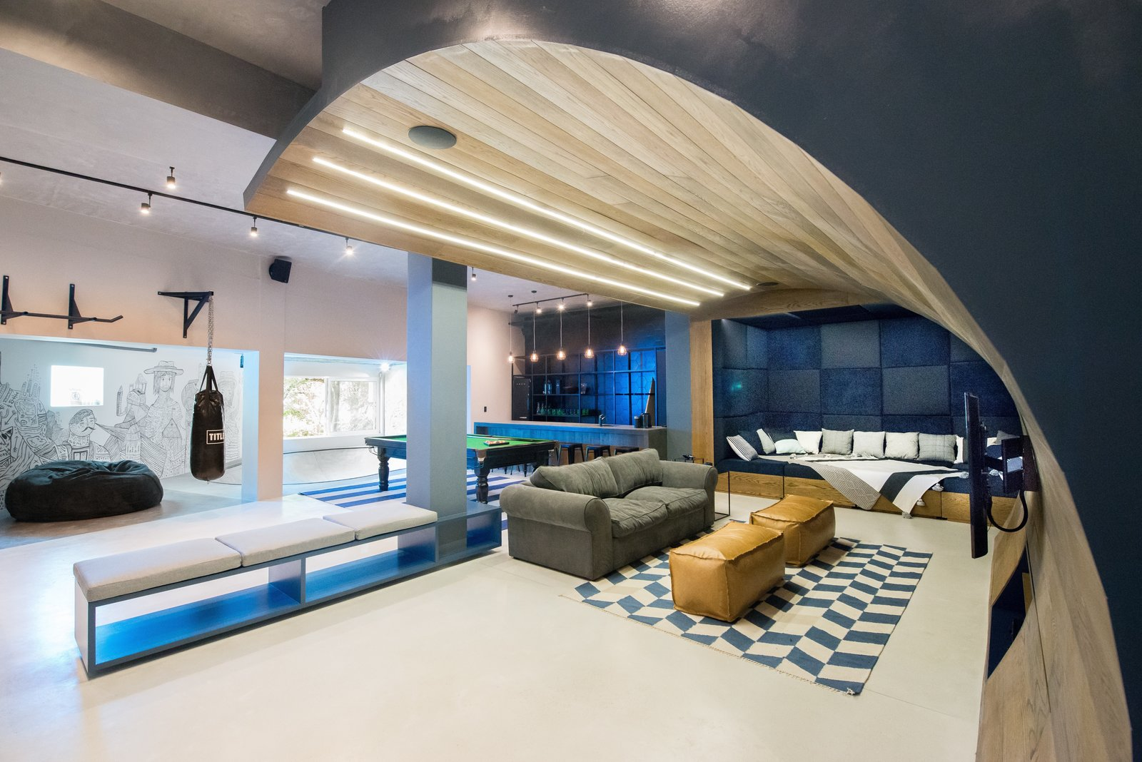 "A movie-watching paradise with a curved timber ""wave"" cascades from the ceiling to the floor. A Skateboarding Devotee Gets the Lounge of His Dreams - Photo 4 of 6"