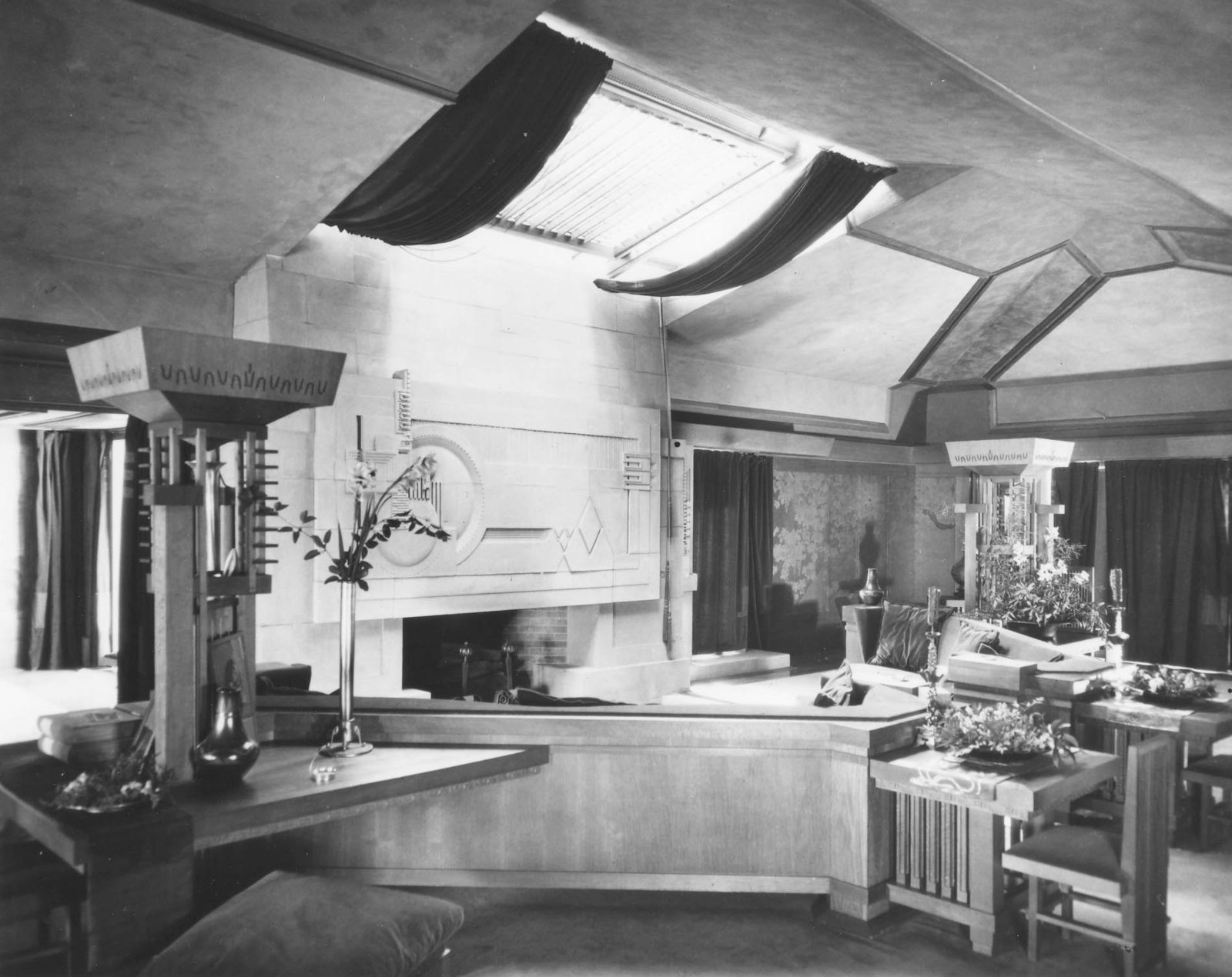 """The Hollyhock House reveals Wright's usage of an open concept plan and reminds us of how he was a master manipulator of space. As seen in this archival image of the living room, it became one of his most influential projects that spread the idea throughout the architectural community. Our tour guide—also known as our """"docent""""—described to us, """"For Wright, compression was always followed by relief. After passing through low entry hallways and multiple columns, you then enter large open spaces through dramatic entrances."""""""
