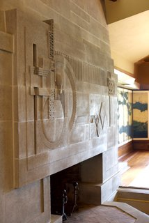 Iconic Perspectives: Frank Lloyd Wright's Hollyhock House - Photo 5 of 13 - One of the standout moments in the space is the cast-concrete fireplace, which is considered to be one of Wright's greatest two-dimensional works of art. He completed the fireplace, a skylight above, and a moat that was designed to hold a pool of water. This was originally part of an elaborate water scheme to run through the property, though it was never completed.