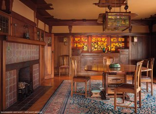 Iconic Perspectives: Greene & Greene's Gamble House - Photo 4 of 7 - Also found throughout the house are complete collections of art tile, pottery, and art glass that were compiled by the resident family. The Greene brothers took these key pieces into consideration when designing the house, and they still exist there today. This dining space reveals a smooth, velvety glow that permeates the space, which is created by a lack of direct lighting. The walls are covered with canvas, which were varnished into a wet plaster.