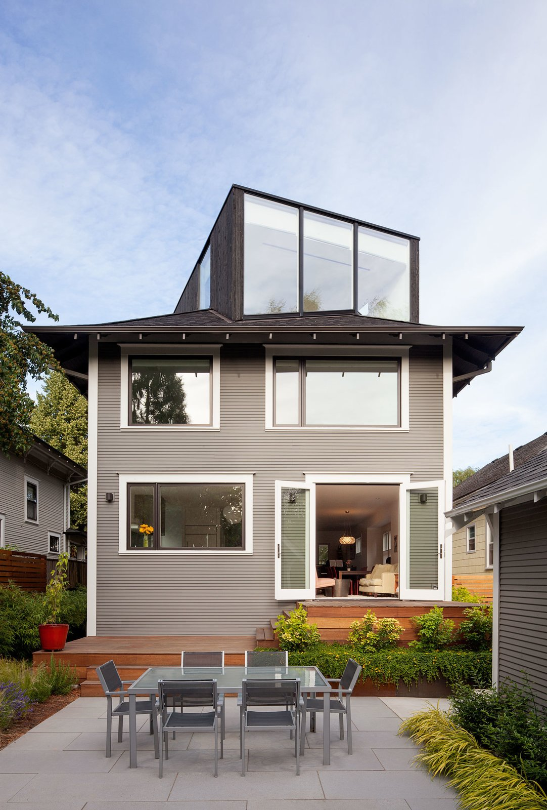 """Thomas Robinson of LEVER Architecture restored the exterior of the house in order to resurface the original wood facade, which had been covered up by vinyl siding at one point. They turned the unused attic into a """"FifthSquare"""": a box-like structure that acts as an office and mini-theater, complete with a ceiling-mounted projector and drop-down screen. The exterior of the extension is clad with charred cedar, which integrates smoothly into the asphalt shingle roof.  house pics by Joseph Fields from Dwell Home Tours Makes its Way to Portland"""