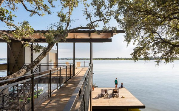 The three-story Blue Lake Retreat is located in Marble Falls, Texas. The residence was designed by Lake Flato Architects to integrate naturally into the steep topography. With living spaces on the top floor and four bedrooms on the two lower floors, the timber structure is connected to the hillside by a bridge and boasts a cantilevered deck that floats just above the lake.