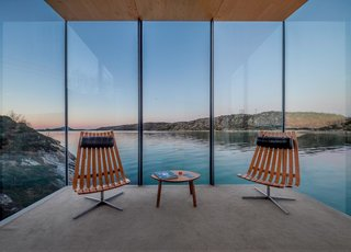 The large expanses of glass were designed specially to frame the seaside views. To fit with the minimal aesthetic of the cabins, the seating areas are furnished with Scandia lounge chairs that were designed by Hans Brattrud in the 1950s and that are now being produced by Fjordfiesta.