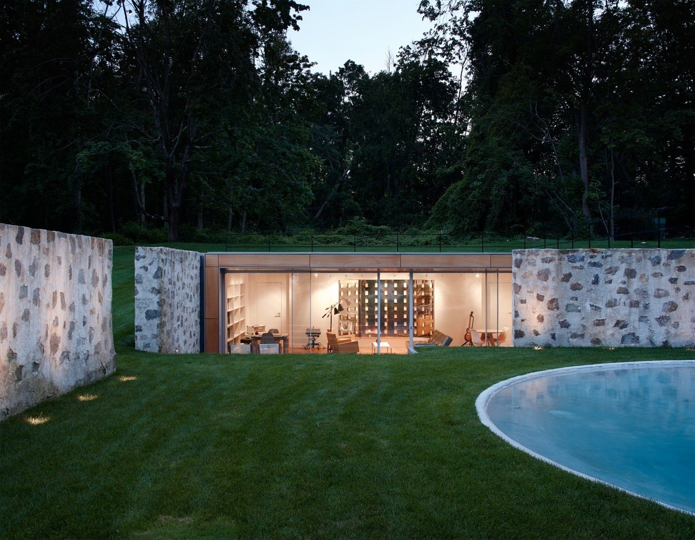 Taking a peek into the new pool house that helps enclose the area, you can see how the sloped land and the original stone walls allow it to remain surprisingly hidden from the outside.  Photo 6 of 10 in After a Year on the Market, Philip Johnson's Wiley House Drops by $2 Million