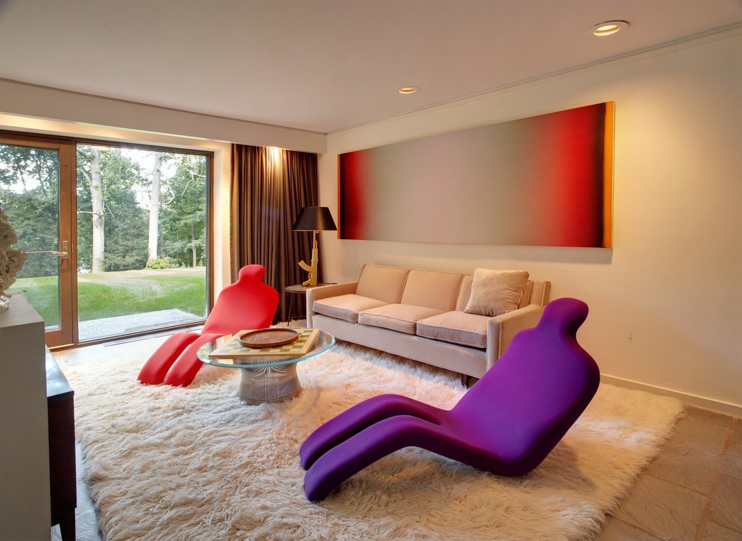 Shown here is the sitting room in the bottom half of the main house. As an art collector, the current homeowner has filled the entire interior with bold statement pieces.
