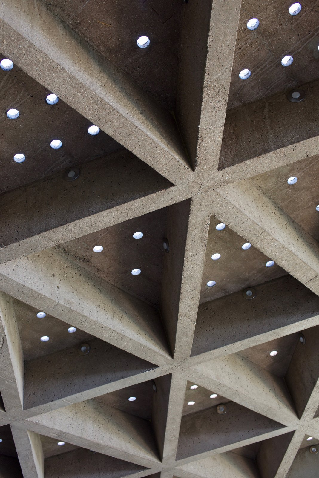 The ceiling is covered with sandblasted concrete that still has the original miniature circular skylights. Behind the Scenes at John Lautner's Sheats-Goldstein Residence by Paige Alexus