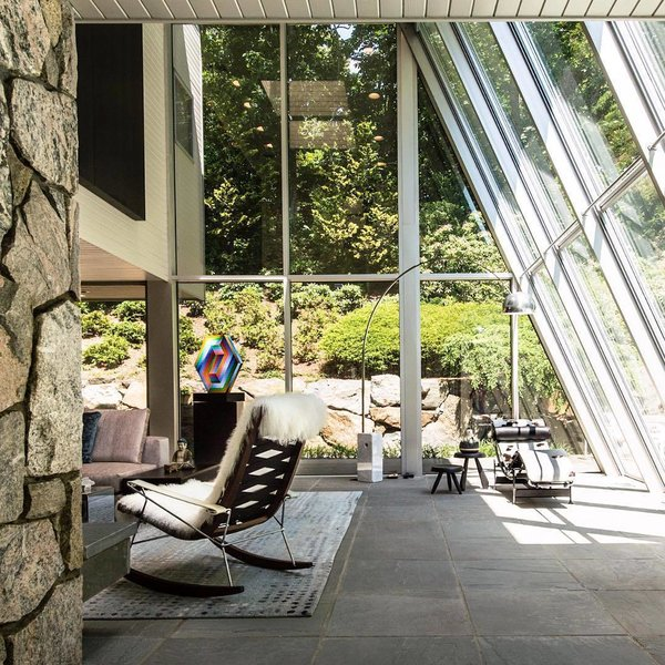 10 Enclosed Porches That Are Put to Good Use - Photo 3 of 10 - New York-based design firm Mojo Stumer Associates sent us a look into a home renovation they completed in Laurel Hollow, New York. With an interior that features a mix of textured fabrics and stone, they formed multiple seating areas throughout the glass-enclosed living space.