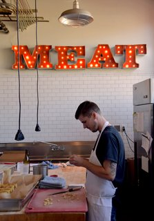 "A Weekend in Portland: Part II - Photo 5 of 10 - This Olympia Provisions location is hidden inside a restored industrial building in a part of town that's held strong onto its industry-filled history. Visitors can take a peek into the kitchen where snacks and entrees are prepared under a glowing industrial ""MEAT"" sign."