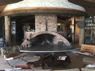 Iconic Perspectives: Harry Gesner's Sandcastle - Photo 4 of 8 - The main house rotates around a large fireplace, where Gesner's late wife Nan Martin used to perform for friends and family. The bones of the space is made up of old-growth redwood that was cut in the 1800s, reused telephone poles, and reclaimed wood that's been turned into door frames, window frames, and floors.