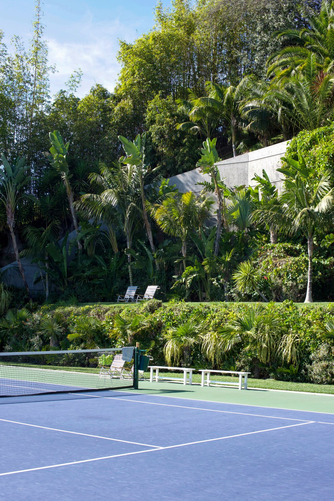 Goldstein's jungle extends over four acres of the property and lines the infinity tennis court.  Behind the Scenes at John Lautner's Sheats-Goldstein Residence by Paige Alexus