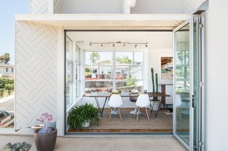 This San Diego Beach House is Stacked With Charm - Photo 2 of 2 - Sitting on the ground floor is the dining area, which they elevated in order to take advantage of natural light and to have access to the outdoor deck.
