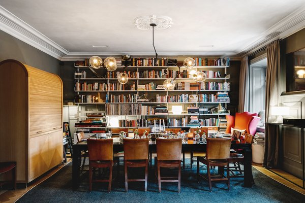 A Visual Journey Through Stockholm's Hotel Ett Hem - Photo 2 of 12 - In the formal dining area, guests are invited to make themselves at home. The floor-to-ceiling bookcases create an intimate dining experience, which sits under original decorative ceiling details.